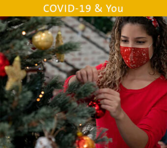 Woman wearing face mask decorating Christmas tree