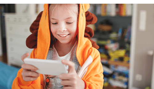 Child wearing costume while looking at smartphone