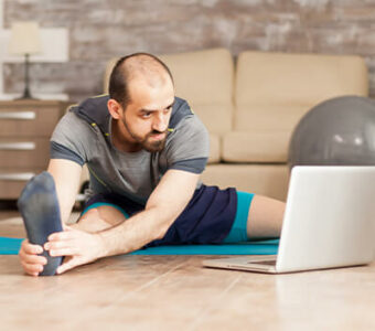Man exercising while looking at laptop for workout guidance