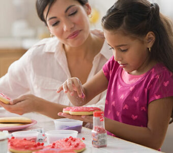 Mother and child decorating pink heart cookies for Valentine's Day